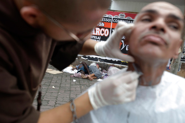 """Брат Пласидо из францисканского братства """"Путь"""" бреет бездомного мужчину. Фото: Ricardo Moraes/Reuters (BRAZIL)"""