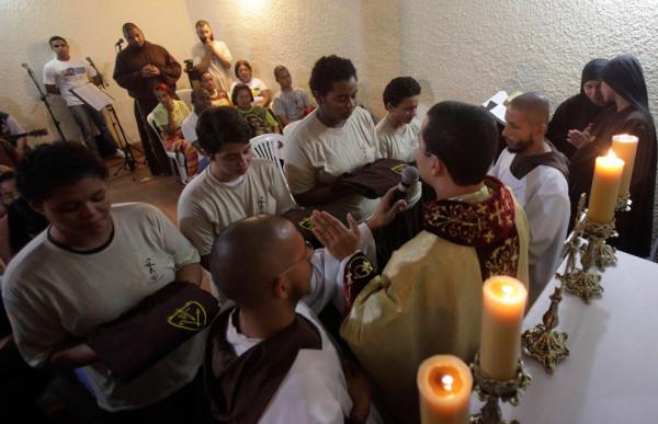 Члены братства, слева направо, Рената Флоренсио, Паллома Баррадас и Хулиана Сантос, получают свои первые облачения во время Святой Мессы в доме братства. Фото: Ricardo Moraes/Reuters (BRAZIL)